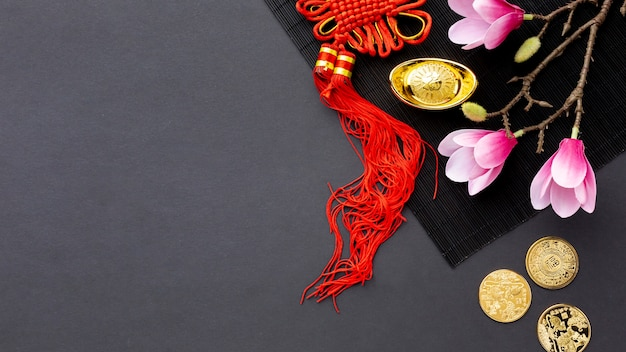 Top view of golden coins and magnolia chinese new year