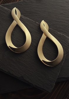 Top view of golden earrings pair on dark stone plate