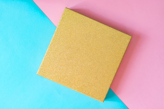 Top view of golden gift box on double pink and blue background. minimal flat lay, creative backdrop with copy space