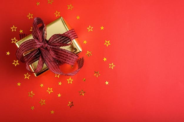 Вид сверху золотой подарочной коробки с бордовым бантом и россыпью золотых звезд конфетти на красном фоне