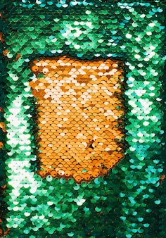 Top view of golden and green textile with shiny sequins as background