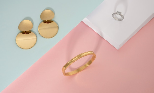 Top view of golden jewelries on pink white and green background