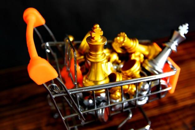 Вид сверху золотые королевские шахматы с шахматными фигурами в маленькой тележке для покупок с деревянным полом в стиле ретро, изолированным на черном