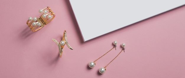 Top view of golden and pearl bracelets and earrings on pink surface