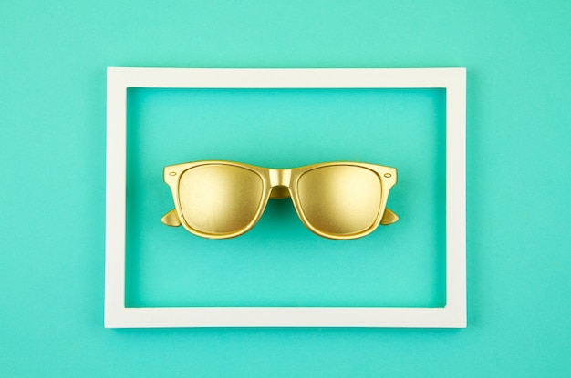 Top view of golden trendy sunglasses over the pastel turquoise background