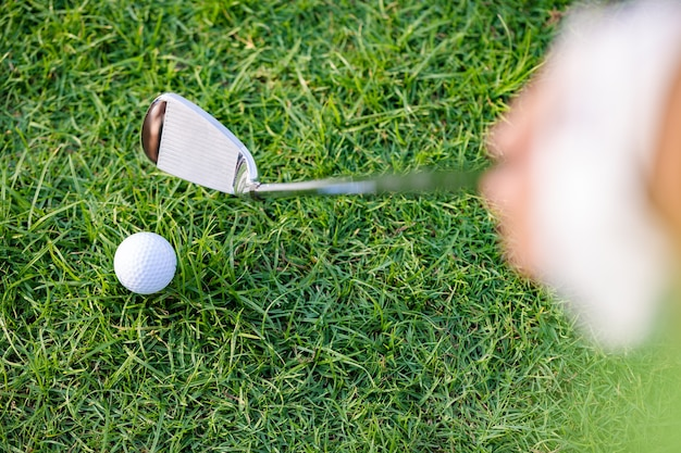 Top view of golf clubs and golf balls on a green lawn in a beautiful course with morning