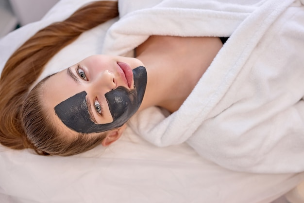 Top view on good-looking cute female with black facial mask on half of face