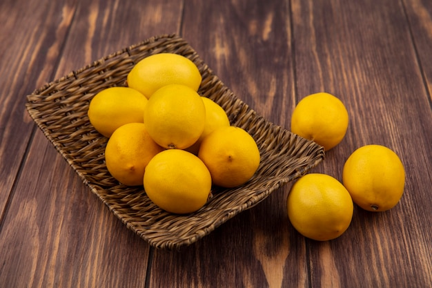 Top view of a good source of vitamin c lemons on a wicker tray with lemons isolated on a wooden surface