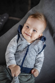 Top view of gorgeous caucasian toddler smiling, lying on couch and playing with his foot.