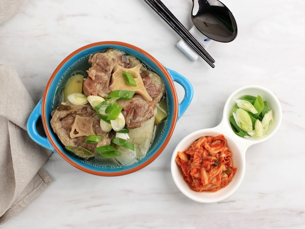 탑뷰 고리곰탕(속꼬리 곰탕 또는 꼬리) 또는 한우 소꼬리 찌개, 김치와 파 썰은 푸른 그릇에 제공
