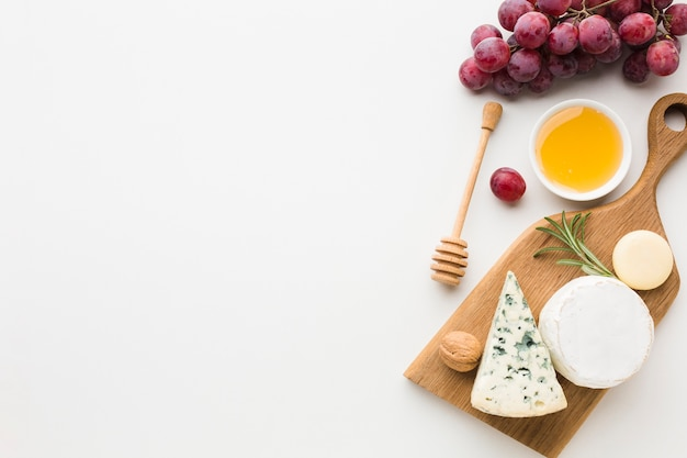 Top view gourmet assortment of cheese on wooden cutting board with copy space