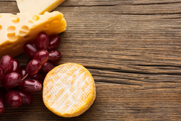 Top view gourmet cheese and grapes with copy space