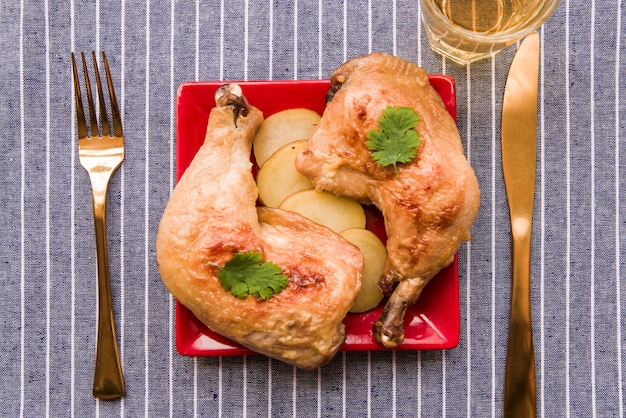 Top view of gourmet roasted chicken leg on plate with fork and butter knife on table cloth