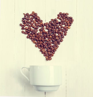 Top view grain of coffee in the form of a heart over a cup.
