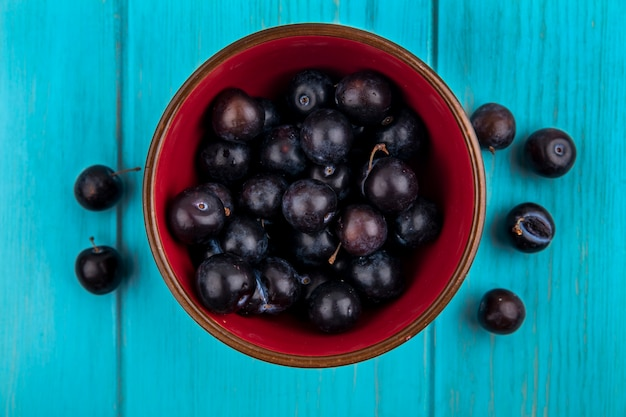 Top view of grape berries in bowl and on blue background