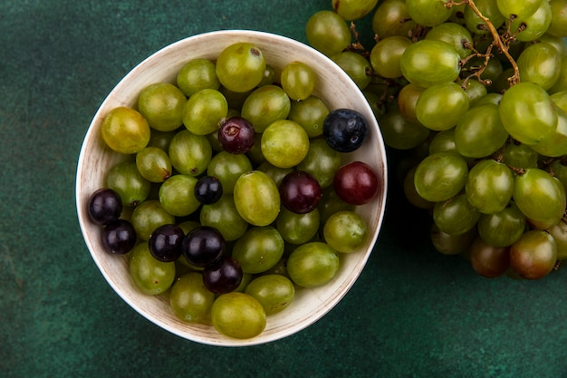 Top view of grape berries in bowl and bunch of grape on green background