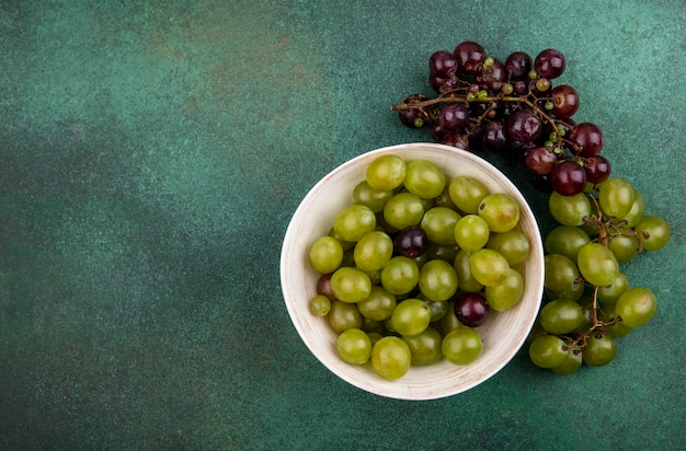 Top view of grape berries in bowl and grapes on green background with copy space