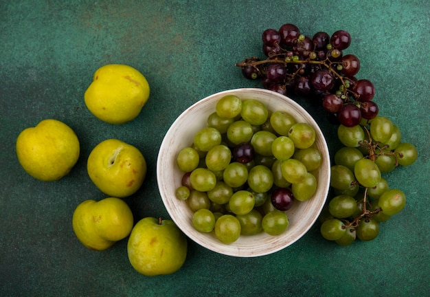 Top view of grape berries in bowl and grapes with green pluots on green background