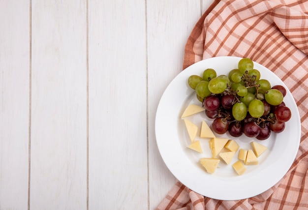 Top view of grape and sliced cheese in plate on plaid cloth on wooden background with copy space