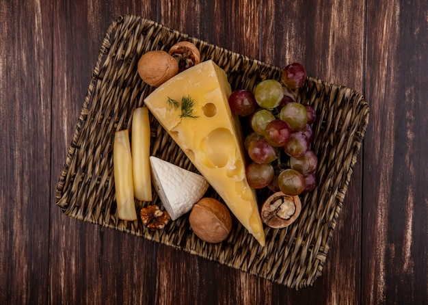 木製の背景のスタンドにさまざまなチーズとナッツのトップビューブドウ