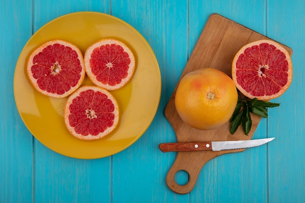 Top view grapefruit on a cutting board with a knife and wedges on a yellow plate  on a turquoise background