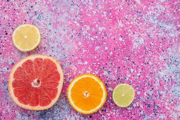 Vista dall'alto anello di pompelmo con fette di arancia e limone sullo sfondo colorato di agrumi di frutta colore esotico