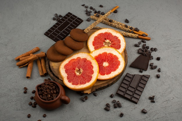 Top view grapefruit sliced along with choco cookies brown coffee seeds choco bars on the grey