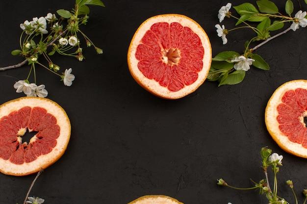 Вид сверху ломтики грейпфрута вместе с белыми цветами на темном полу