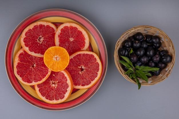 Vista dall'alto fette di pompelmo su un piatto con prugna ciliegia in un cesto su uno sfondo grigio
