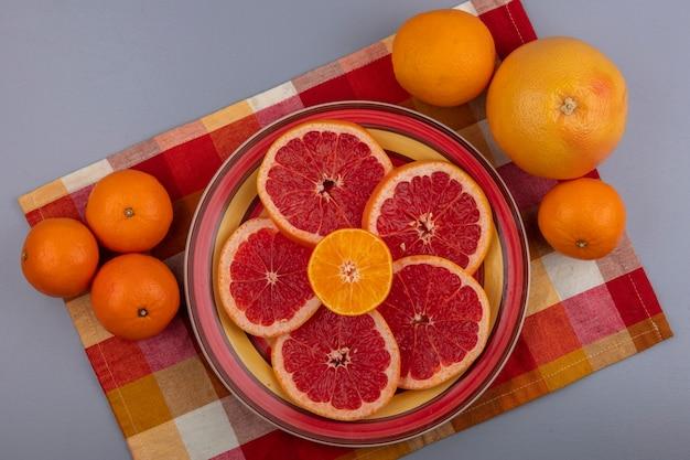 Vista dall'alto fette di pompelmo su un piatto con arance su un asciugamano multicolore a scacchi su uno sfondo grigio