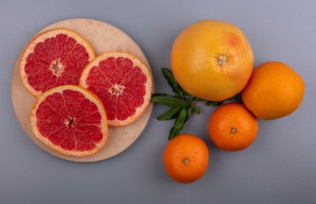 Vista dall'alto fette di pompelmo su un supporto con arance su uno sfondo grigio