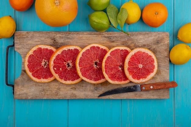 Vista dall'alto spicchi di pompelmo sul tagliere con coltello e limoni con lime e arancio su sfondo turchese