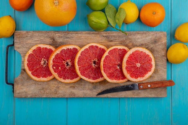 청록색 배경에 라임과 오렌지와 칼과 레몬 커팅 보드에 상위 뷰 자몽 웨지