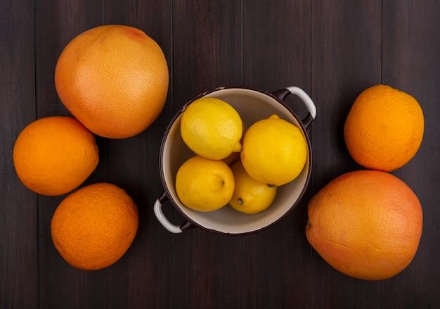 木の背景の上の鍋にオレンジとレモンとグレープフルーツの上面図