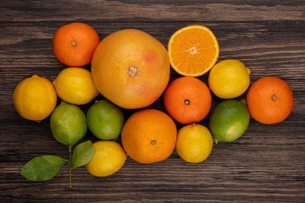 Vista dall'alto pompelmo con arance limoni e limette su fondo in legno