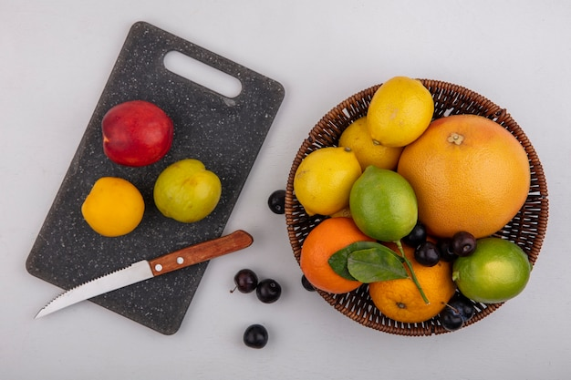 Top view grapefruit with oranges  limes and lemons in a basket with cherry plums and peaches on a cutting board with a knife on a white background