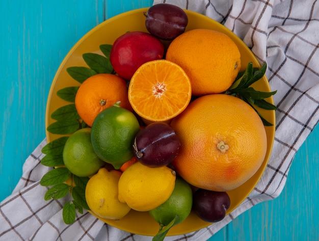 Vista dall'alto pompelmo con arance prugne limoni e limette su una piastra gialla su un asciugamano a scacchi su uno sfondo turchese