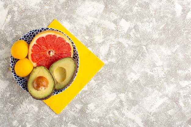Вид сверху грейпфруты и авокадо внутри тарелки на белой поверхности
