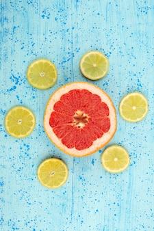 Вид сверху грейпфруты и лимоны спелые кислые спелые нарезанные на ярко-синем фоне