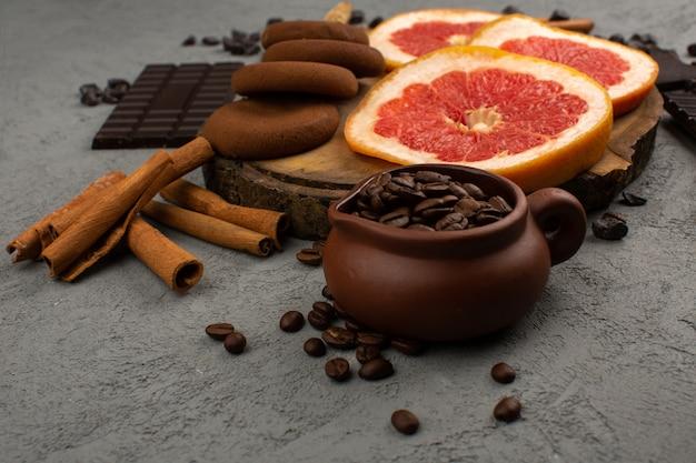 Вид сверху грейпфруты печенье корица вместе с коричневыми семенами кофе на сером полу