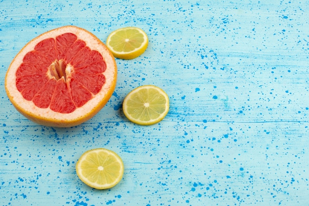 Top view grapefruits and lemons sliced mellow ripe on the bright blue background