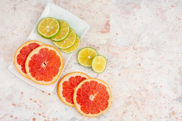 上面図グレープフルーツは、ヌードテーブルの空き領域に白い長方形のプレートにレモンスライスをスライスします