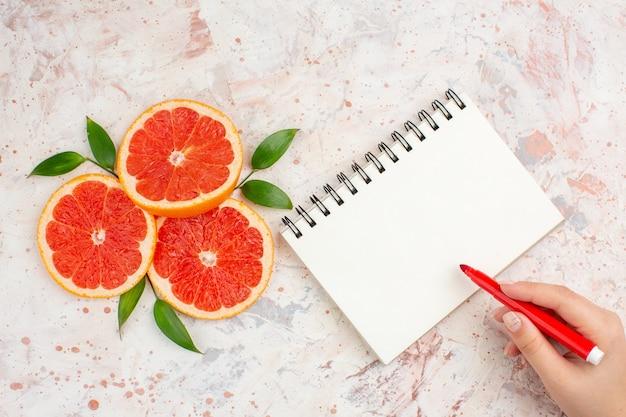 Вид сверху ломтики грейпфрута с листьями блокнот красный маркер в женской руке на обнаженной поверхности