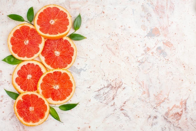 Top view grapefruits slices with leaves on nude surface copy space
