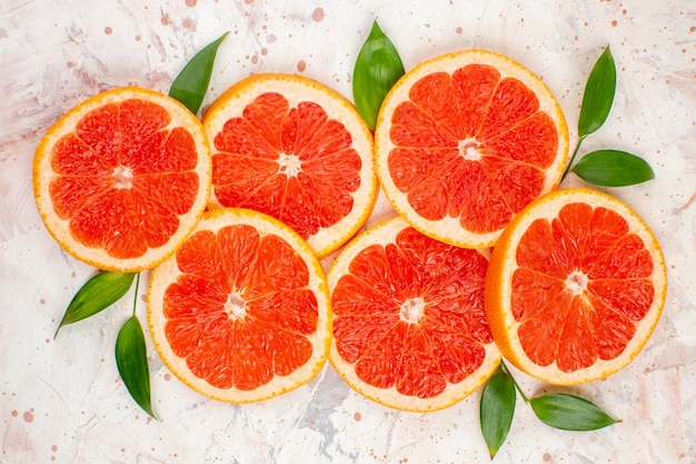 Top view grapefruits slices with leaves on nude surface