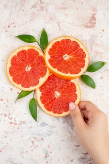 Top view grapefruits slices woman hand taking grapefruit slice on nude surface