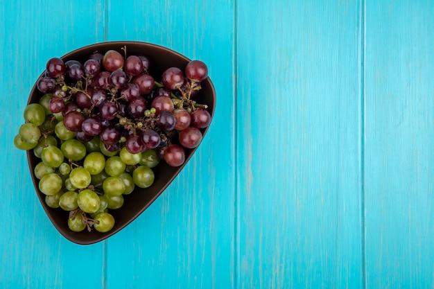Vista dall'alto di uva in una ciotola su sfondo blu con spazio di copia