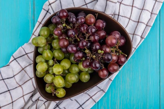 Vista dall'alto di uva nella ciotola sul panno plaid su sfondo blu