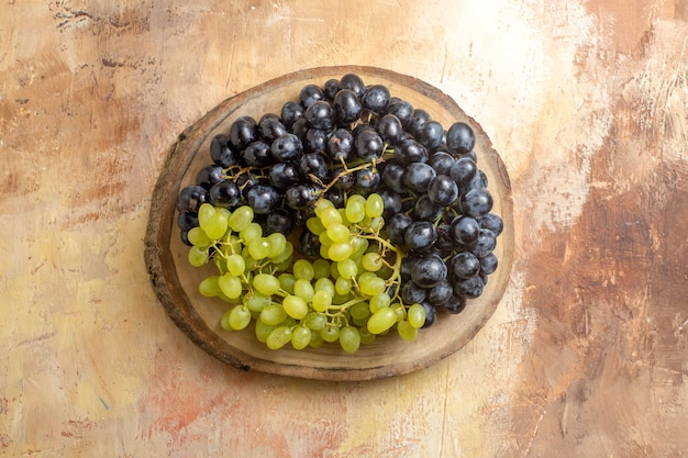 Top view of grapes bunches of green and black grapes on the kitchen board