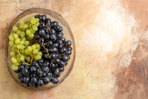 Top view grapes bunches of green and black grapes on the wooden cutting board